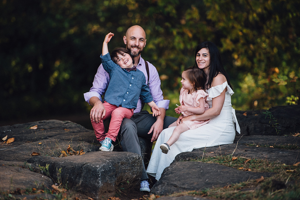 family of four sitting on a rock